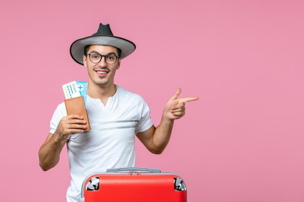 Вид спереди молодого человека, держащего билеты на самолет и собирающегося в отпуск на розовой стене