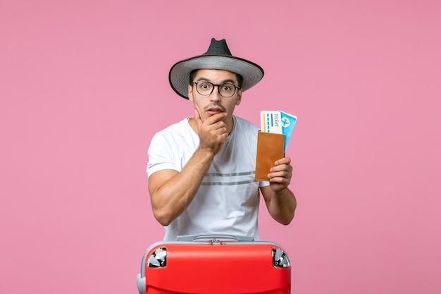 분홍색 벽에서 휴가를 준비하는 비행기 표를 들고 있는 청년의 전면