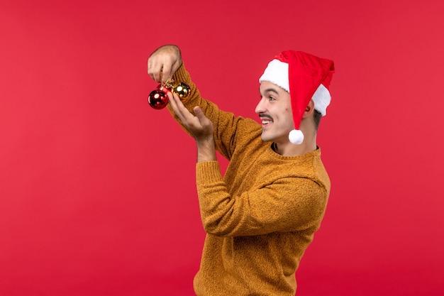 빨간 벽에 플라스틱 장난감을 들고 젊은 남자의 전면보기