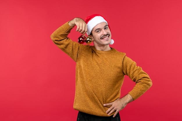 Вид спереди молодого человека, держащего пластиковые игрушки на красной стене