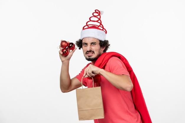 白い壁にプレゼントとおもちゃを保持している若い男の正面図