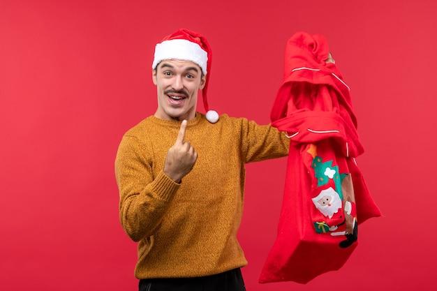 붉은 벽에 선물 가방을 들고 젊은 남자의 전면보기