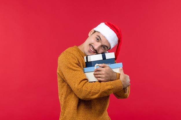 明るい赤の壁にプレゼントボックスを保持している若い男の正面図