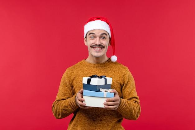赤い壁にプレゼントボックスを保持している若い男の正面図