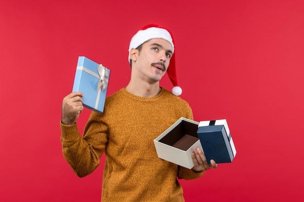 빨간 벽에 선물 상자를 들고 젊은 남자의 전면보기