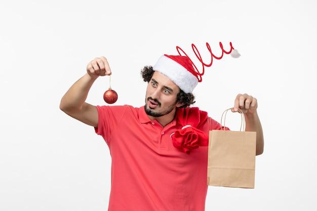 흰 벽에 패키지에 선물을 들고 있는 젊은 남자의 전면 보기
