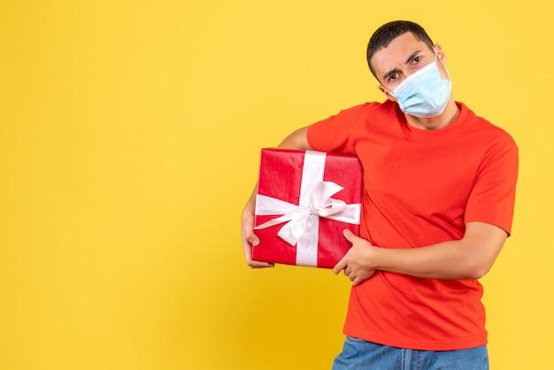 Вид спереди молодого человека, держащего в стерильной маске на желтой стене