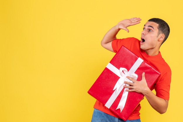 노란색 벽에 놀란 표정으로 선물을 들고 젊은 남자의 전면보기