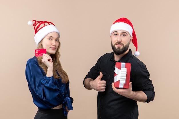 분홍색 벽에 은행 카드를 들고 여자와 선물을 들고 젊은 남자의 전면보기