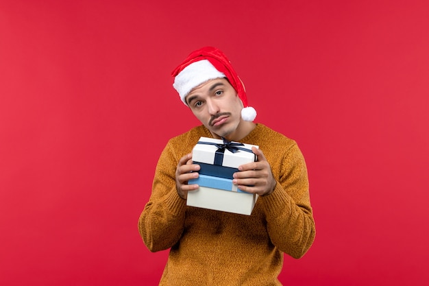 赤い壁にプレゼントを保持している若い男の正面図