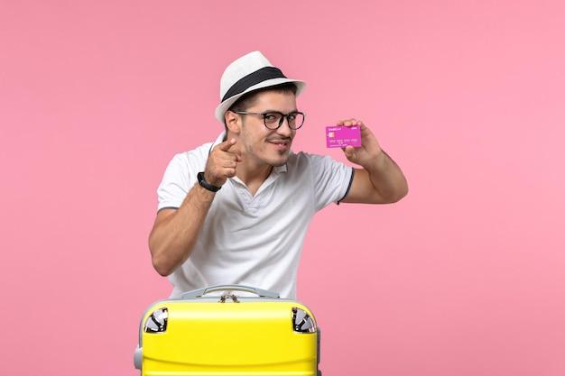 ピンクの壁に夏休みに紫色の銀行カードを保持している若い男の正面図