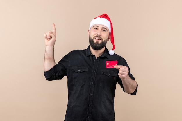 ピンクの壁に赤い銀行カードを保持している若い男の正面図