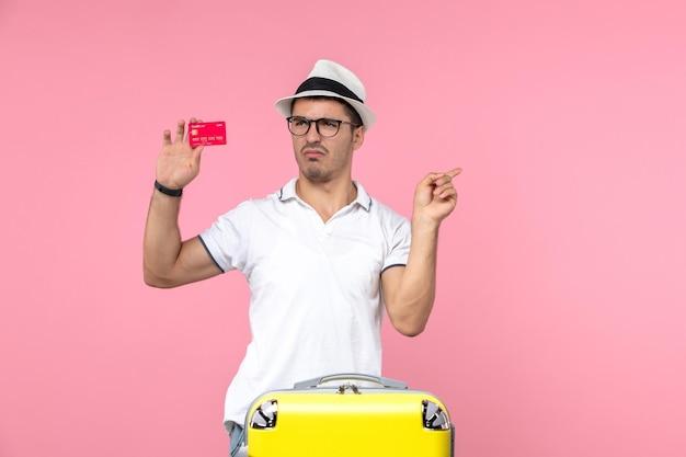 분홍색 벽에 빨간 은행 카드를 들고 있는 젊은 남자의 전면 모습