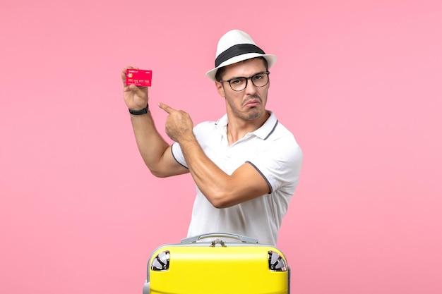 ピンクの壁に休暇で赤い銀行カードを保持している若い男の正面図