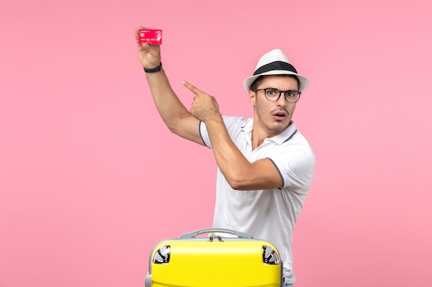 Вид спереди молодого человека, держащего красную банковскую карту в отпуске на розовой стене