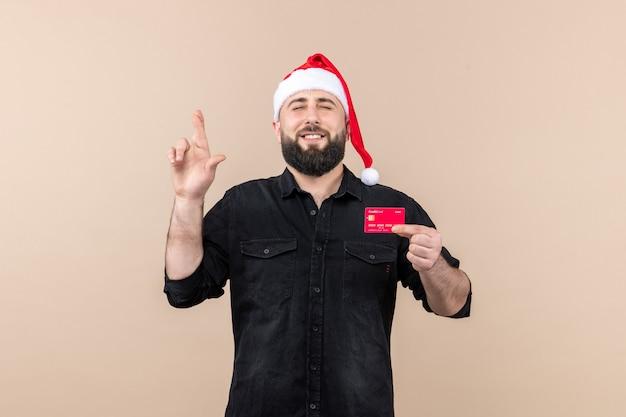 ピンクの壁に笑みを浮かべて赤い銀行カードを保持している若い男の正面図