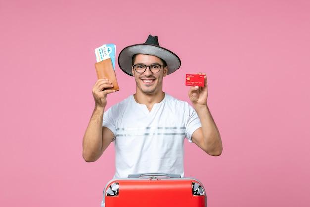 Вид спереди молодого человека, держащего билеты и банковскую карту на розовой стене