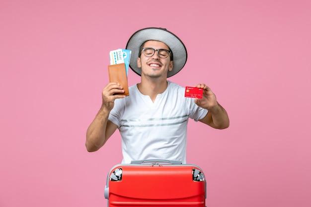 淡いピンクの壁にチケットと銀行カードを保持している若い男の正面図