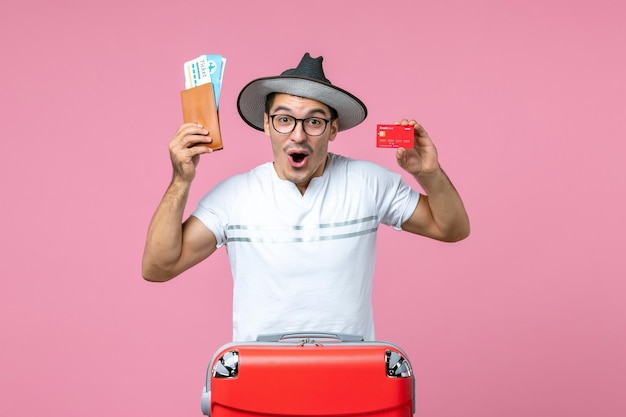 밝은 분홍색 벽에 티켓과 은행 카드를 들고 있는 젊은 남자의 전면 보기