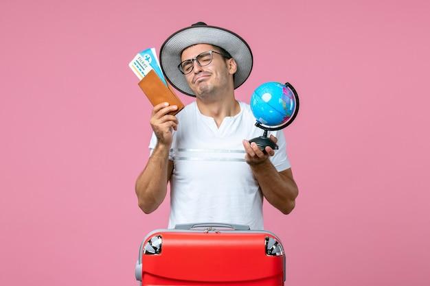 ピンクの壁にチケットと小さな地球儀を保持している若い男の正面図
