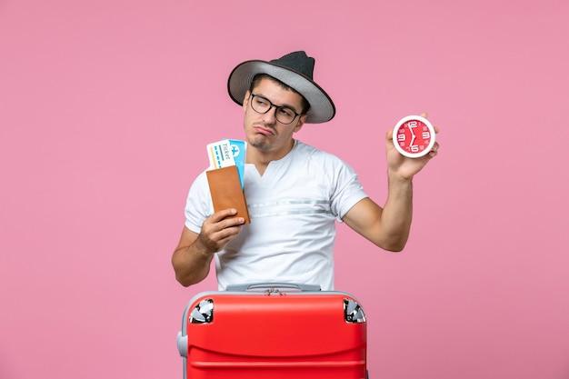 Вид спереди молодого человека, держащего отпускные билеты и часы на розовой стене
