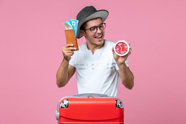분홍색 벽에 휴가 티켓과 시계를 들고 있는 청년의 전면