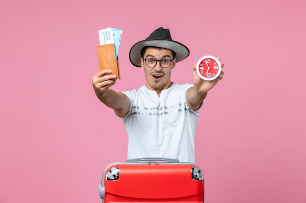 ピンクの壁に休暇のチケットと時計を保持している若い男の正面図