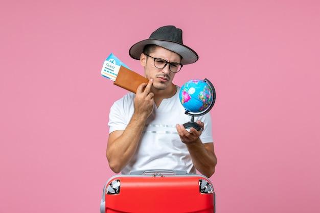 ピンクの壁に休暇のチケットと小さな地球を保持している若い男の正面図