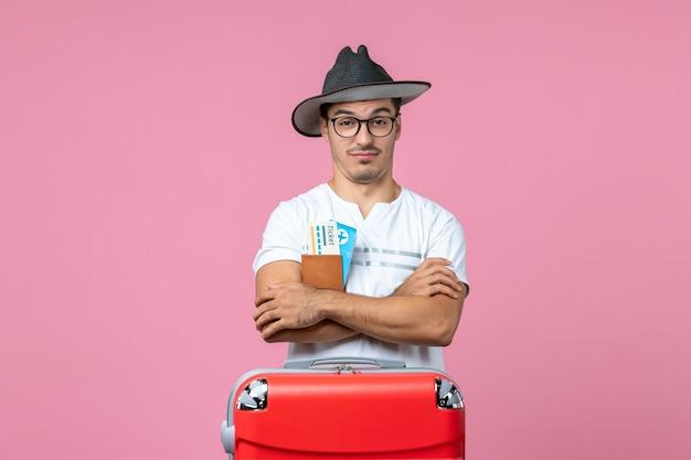 분홍색 벽에 지갑 안에 휴가 티켓을 들고 있는 젊은 남자의 전면 보기