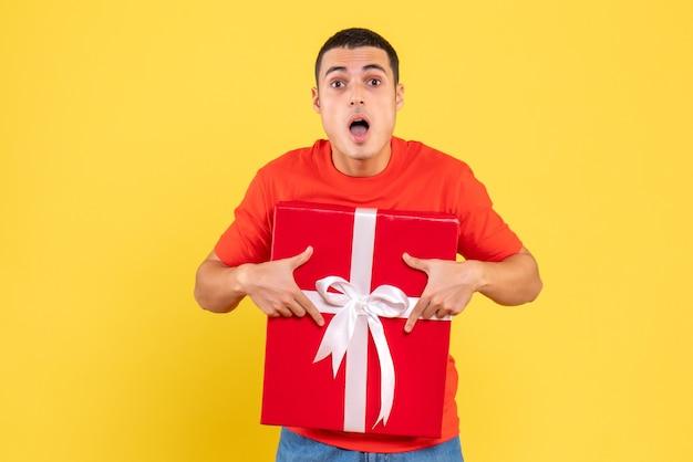 노란색 벽에 놀란 표정으로 선물 크리스마스를 들고 젊은 남자의 전면보기