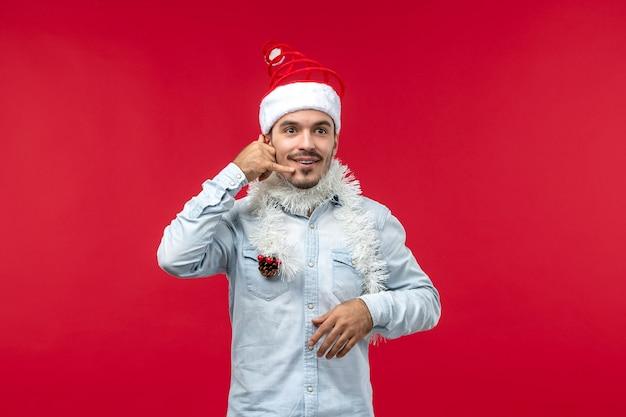 赤い壁に電話を模倣して若い男の正面図