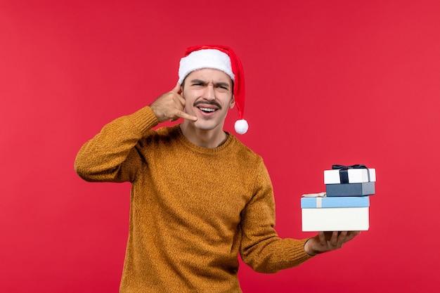 붉은 벽에 전화를 모방하는 젊은 남자의 전면보기