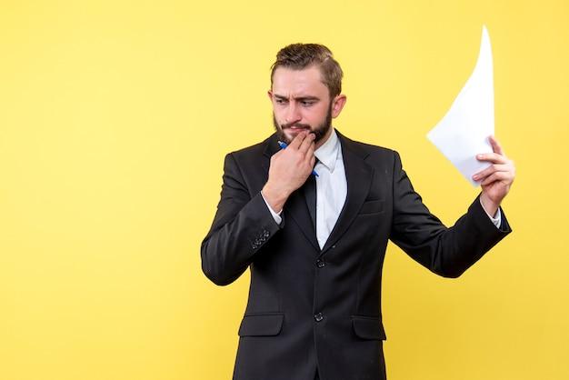 仕事を考えて、黄色で下側を見下ろしているあごに手をつないで黒いスーツを着た若い男の正面図