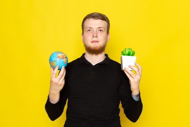 小さな地球と植物を保持している黒いシャツの若い男の正面図