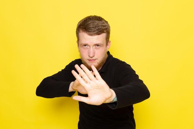 Вид спереди молодого человека в черной рубашке позирует держать социальную дистанцию