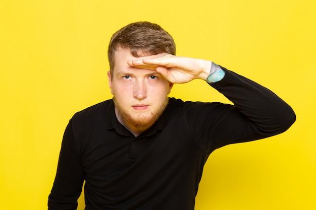 Вид спереди молодого человека в черной рубашке, позирует, глядя вдаль