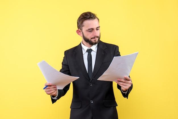 노란색에 문서를 확인하는 검은 양복에 젊은 남자의 전면보기