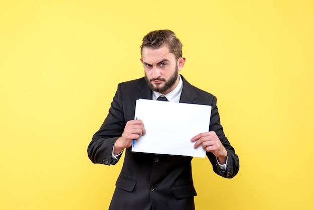 黄色のテキストの場所と白い白紙のシートを保持している真剣な黒のスーツを着た若い男の正面図
