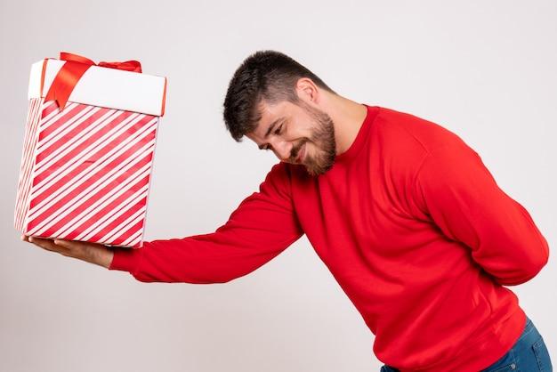 Вид спереди молодого человека в красной рубашке, дающего рождественский подарок в коробке на белой стене