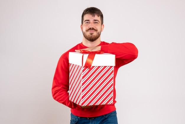 Вид спереди молодого человека в красной рубашке, держащего рождественский подарок в коробке на белой стене