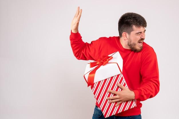 흰 벽에 상자에 크리스마스 선물을 들고 빨간 셔츠에 젊은 남자의 전면보기