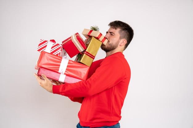 Вид спереди молодого человека в красной рубашке, держащего рождественские подарки на белой стене