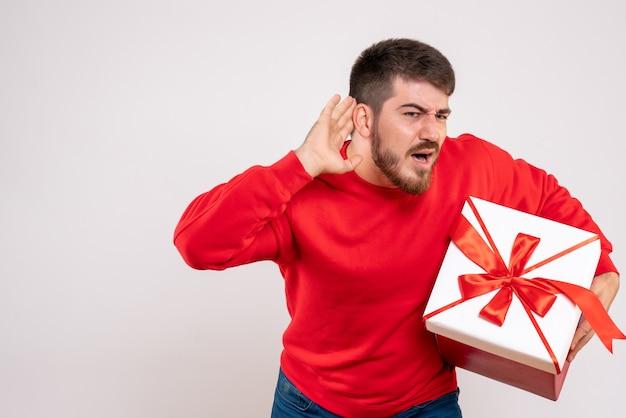 Вид спереди молодого человека в красной рубашке, держащего рождество в коробке на белой стене