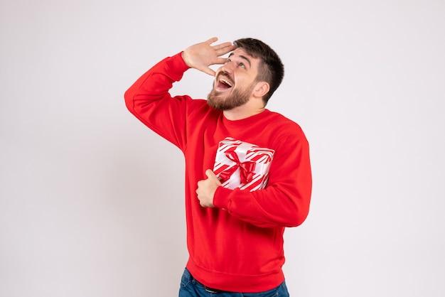 흰 벽에 크리스마스 선물을 들고 빨간 셔츠에 젊은 남자의 전면보기