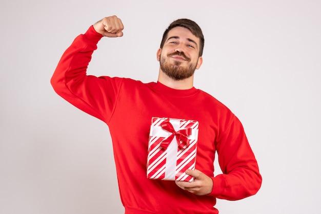 Вид спереди молодого человека в красной рубашке, держащего рождественский подарок на белой стене