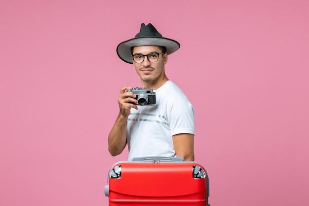 ピンクの壁にカメラで写真を撮る夏休みの若い男の正面図