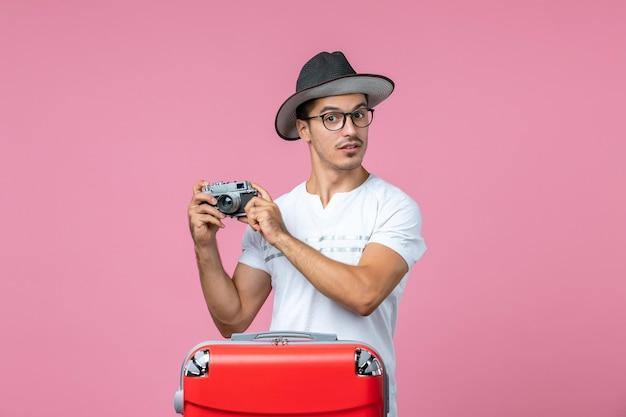 ピンクの壁に写真を撮るカメラを保持しているバッグと休暇中の若い男の正面図