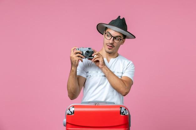 분홍색 벽에 사진을 찍는 카메라를 들고 가방을 들고 휴가 중인 청년의 전면