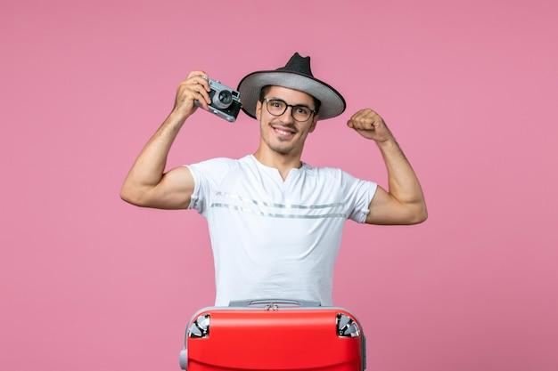 ピンクの壁にカメラで写真を撮るバッグと休暇中の若い男の正面図