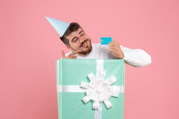분홍색 벽에 은행 카드를 들고 선물 상자 안에 젊은 남자의 전면보기